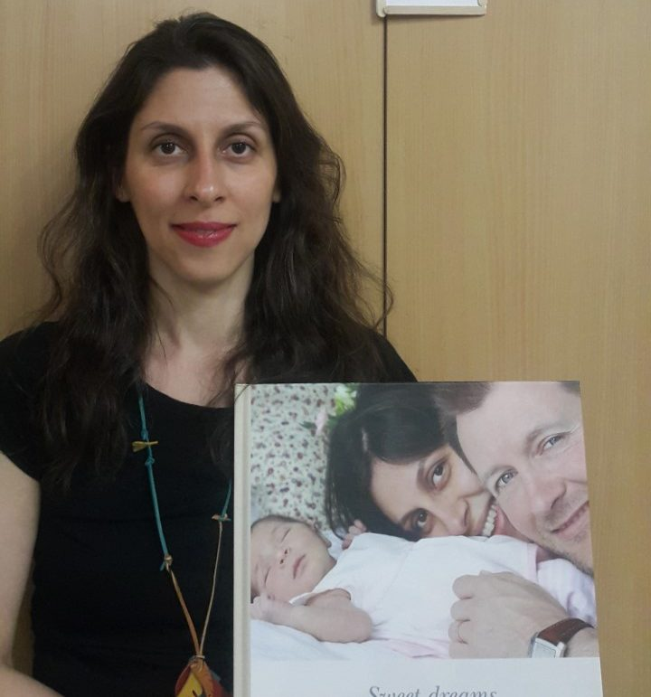 Nazanin Zaghari-Ratcliffe holds a picture of her with her husband and daughter