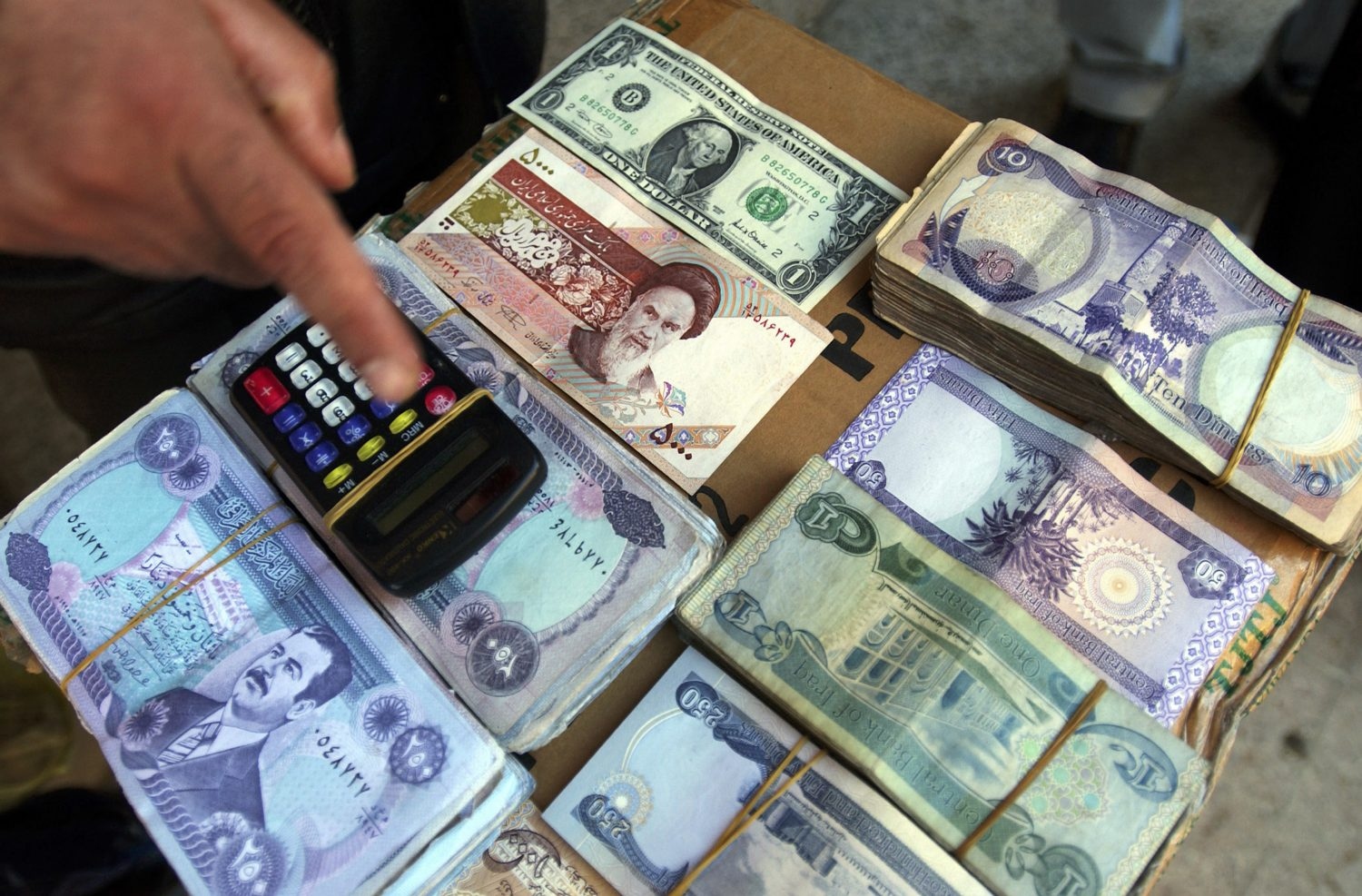 Iraqi, Iranian and American currency being changed on a street stall. Soon the head of Saddam Hussein on Iraqi banknotes will be a thing of the past. The old banknotes are being replaced by new ones.