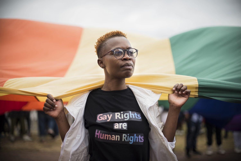 A Lesbian woman holds a rainbow flag at Durban Gay Pride
