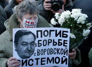 A woman holds a placard with a portrait of Sergei Magnitsky during an unauthorised rally in central Moscow.